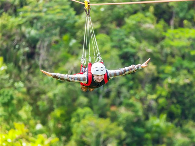 Men enjoying zip-line flying over the forest